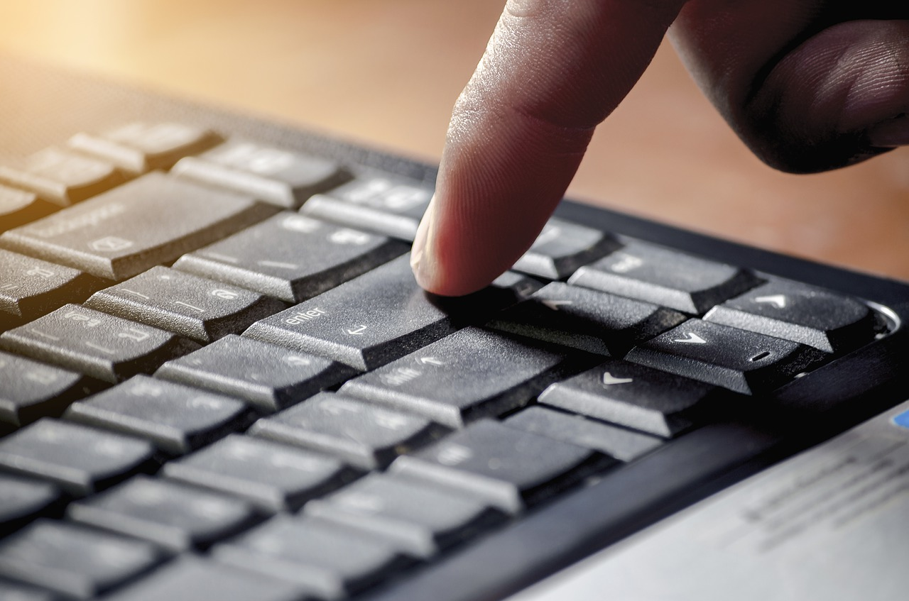 A finger is about to press the enter key on a keyboard