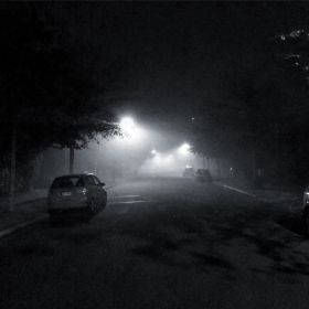 Street lights illuminate the fog and the street during the evening