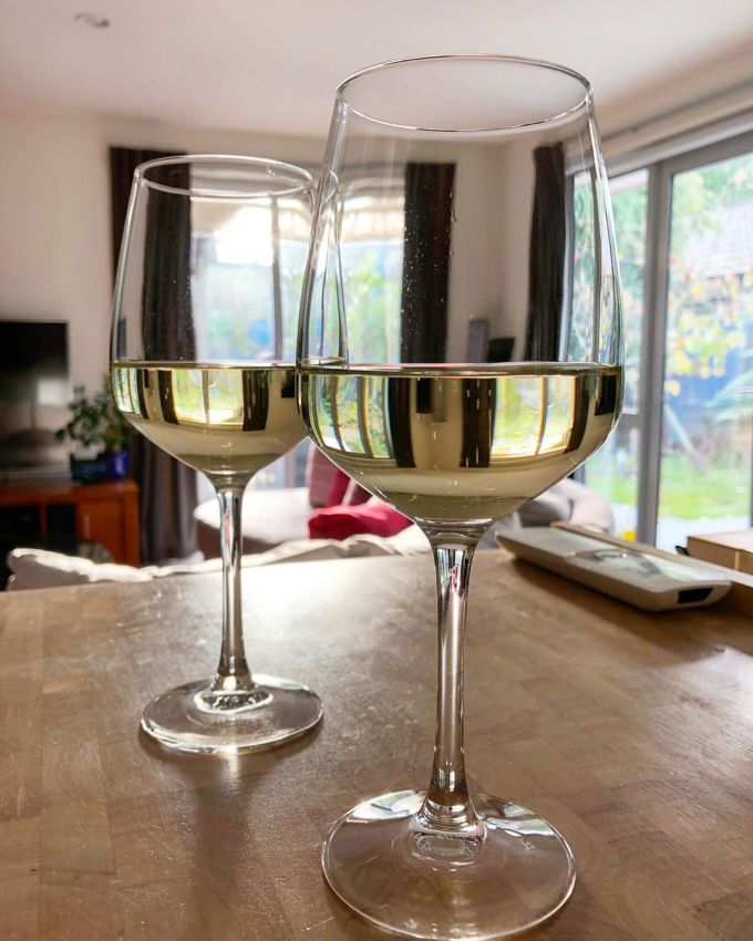 Two wine glasses with champagne in them on a chopping block in a warm, airy, sunny house