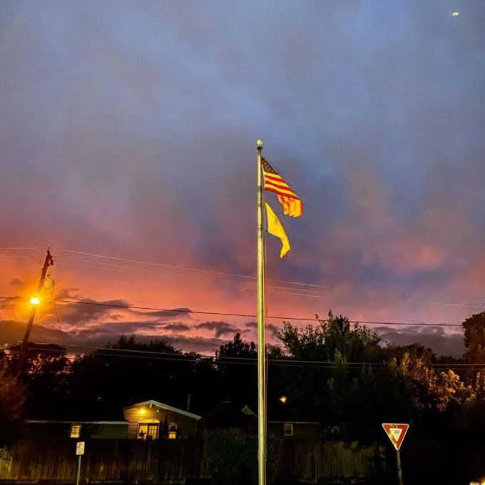 American flag with another flag below it with a sunset in the background