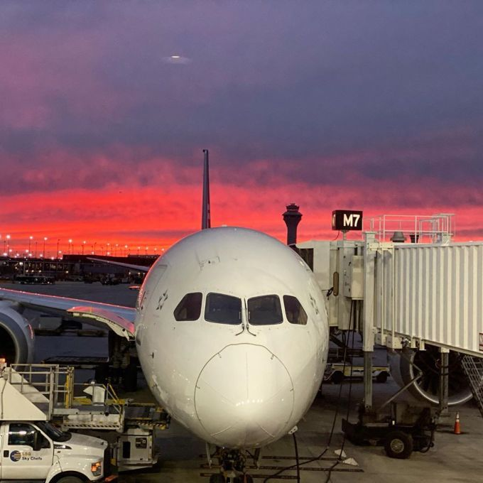 Air New Zealand plane at boarding gate at O'Hare International Airport Terminal 5 with a red sunset in the background