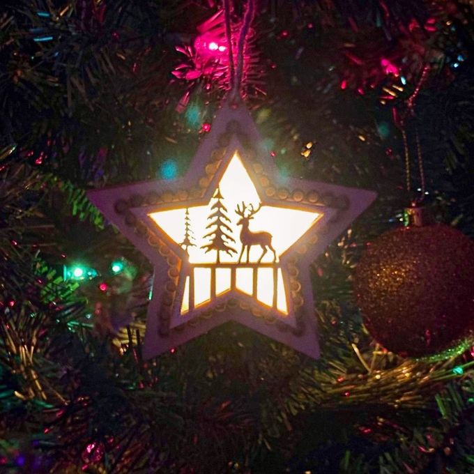 Illuminated Christmas ornament, star-shaped, lit from behind, showing two pine trees and a deer