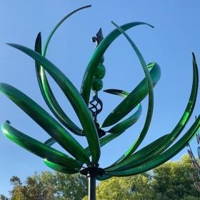 Green metal wind sculpture with blue skies behind it