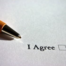"Pen resting on white piece of paper with the words ""I Agree"" and a check box on it"