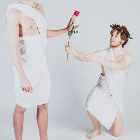 Man giving a rose to another man. Photo by Alessandro De Bellis on Unsplash