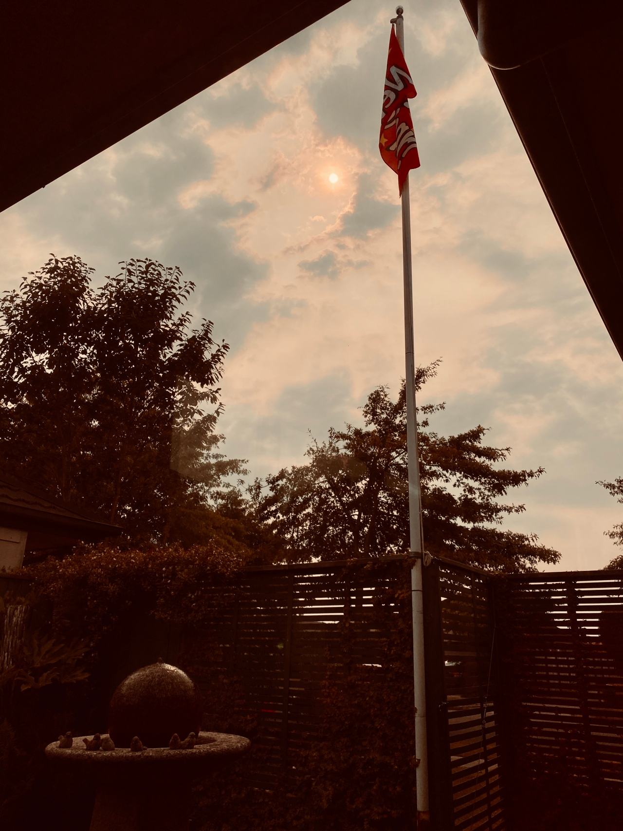Flagpole and yard with sun in the yellow sky on 1 January 2020