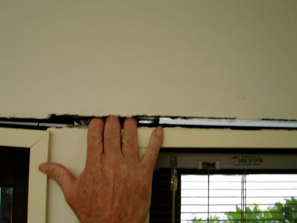 Fingers inside gap between wall and window due to earthquake damage at Unit 7