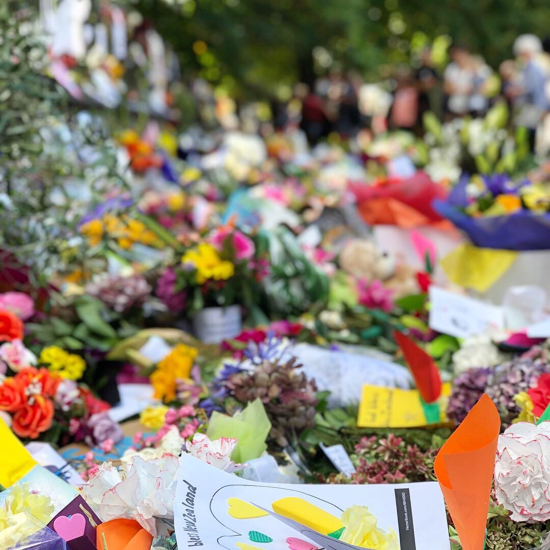 """Floral tributes and signs and a chain of paper humans holding hands on a fence in the Christchurch Botanical Gardens. The main sign is an illustration of Prime Minister Jacinda Adern hugging a woman in a hijab with the words, """"New Zealand is their home. They are us."""""""