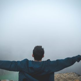 Man stands with arms wide open on a cliff facing a foggy sky