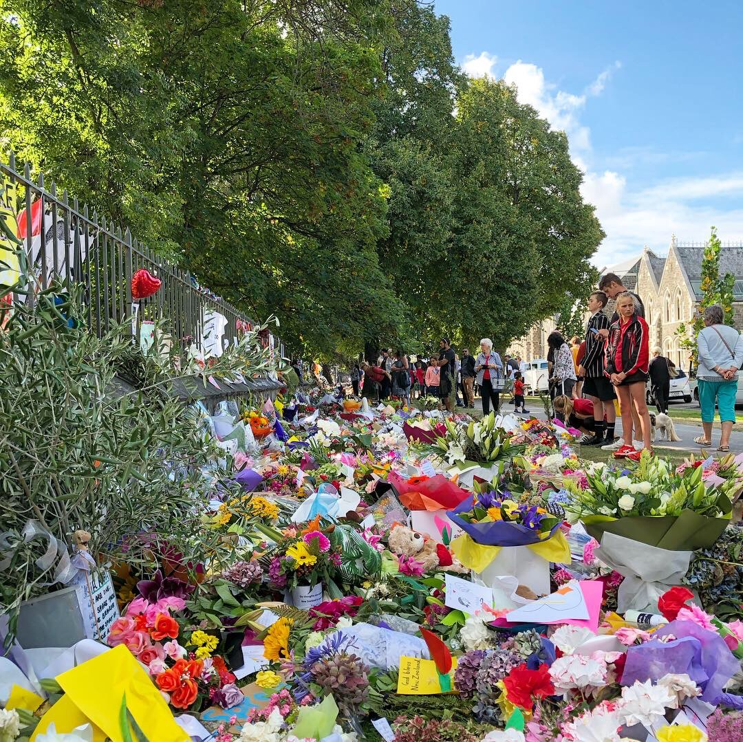 People walk past and pay tribute to the victims of the Christchurch terrorist attacks. There are a deep row of flowers as far as the eye can see pressed up against the fence of the Christchurch Botanical Gardens.