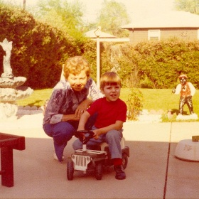 My Grandma squatting down beside me in the mid-70s in their back yard