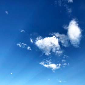 clouds and blue skies with sunshine rays emanating from the corner
