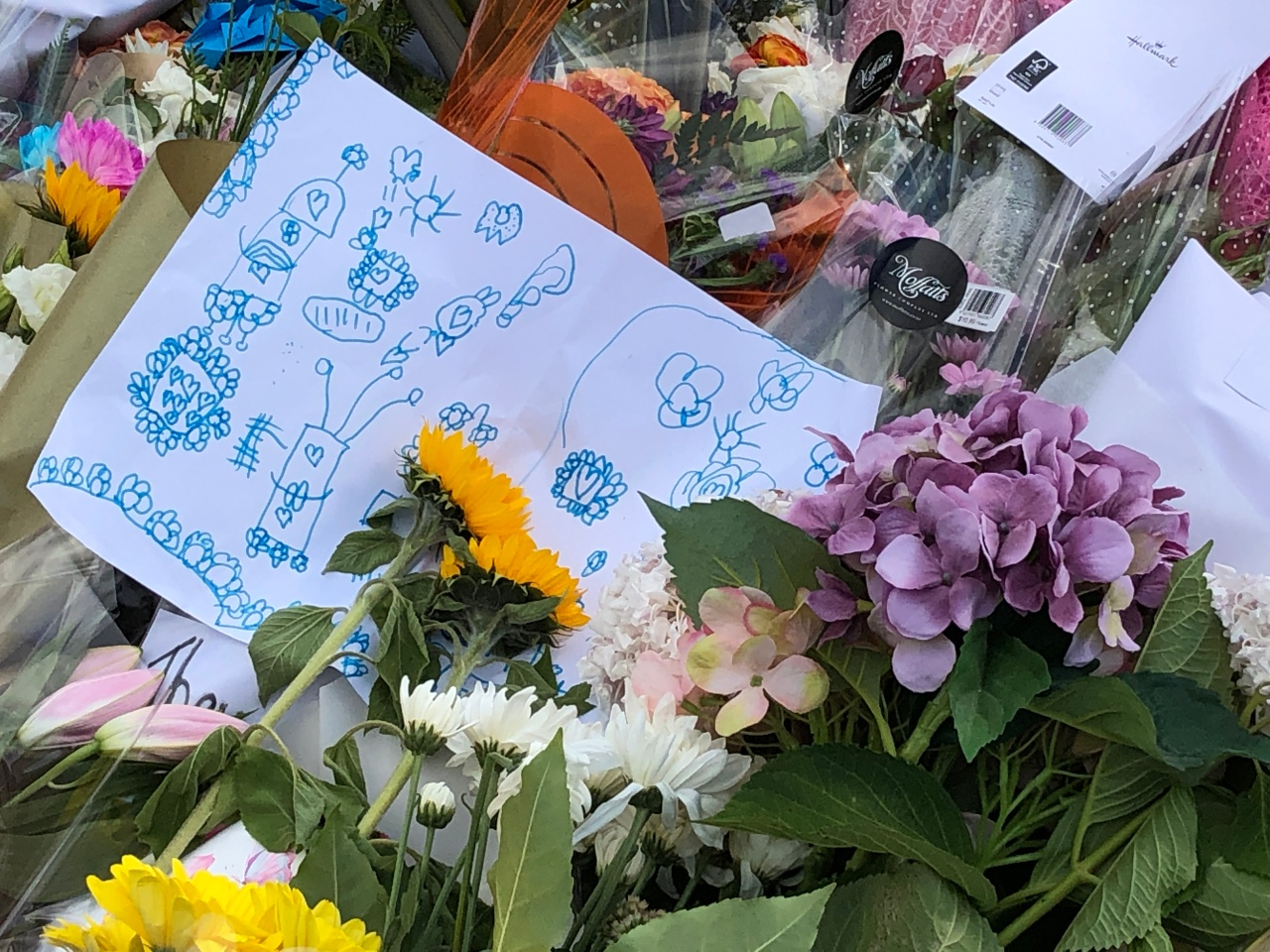 Floral tributes for the victims of the Christchurch terrorist attacks. A child's drawing sits in the middle of many bouquets.