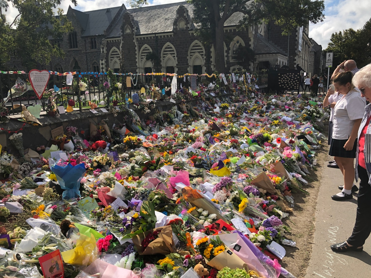 People looking at the massive amount of floral tributes on the ground against the fence at the Christchurch Botanical Gardens for the victims of the Christchurch terrorist attacks.