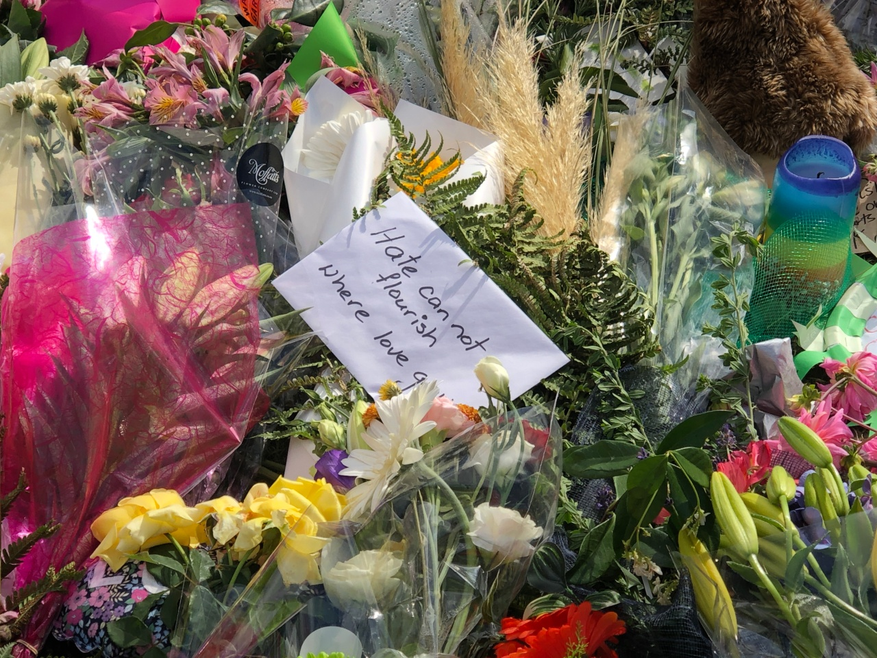 """Several floral tributes for the victims of the Christchurch Terrorist Attacks with a card in the middle saying, """"Hate cannot flourish where love grows."""""""