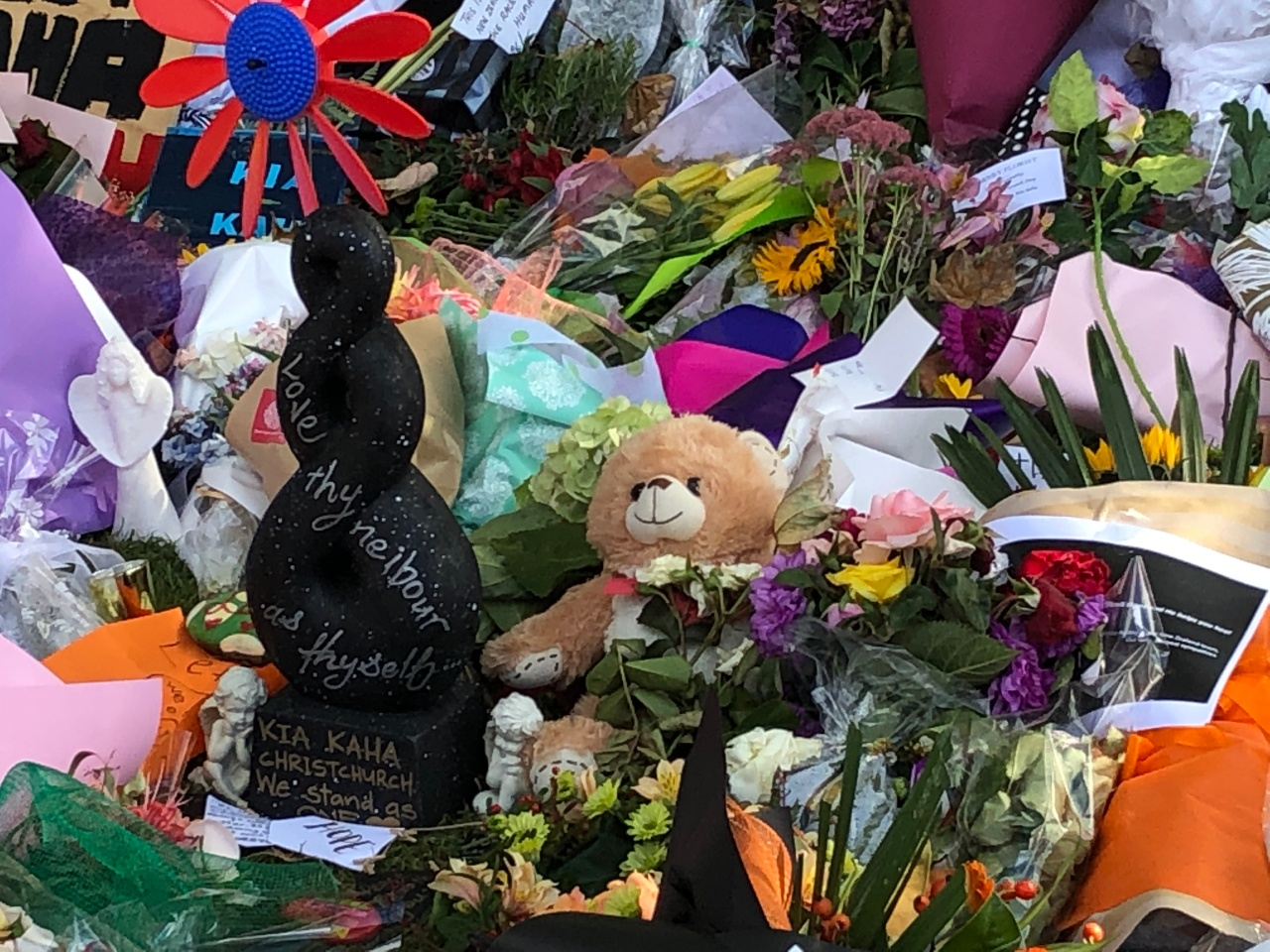 """Many floral tributes for the victims of the Christchurch terrorist attacks, with small statues of angels and a teddy bear. A Maori carving sits in the middle with the words, """"Love thy neighbour and thyself. Kia kaha Christchurch. We stand as one,"""" handwritten on it."""