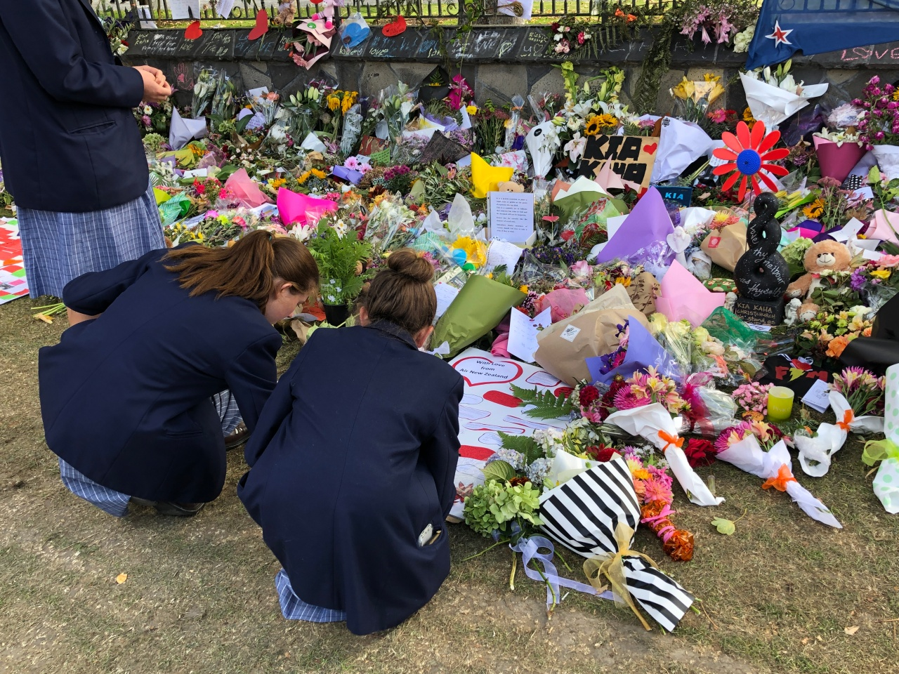 Three high school students write a note on a tribute board surrounded by floral tributes for the victims of the Christchurch terrorist attacks