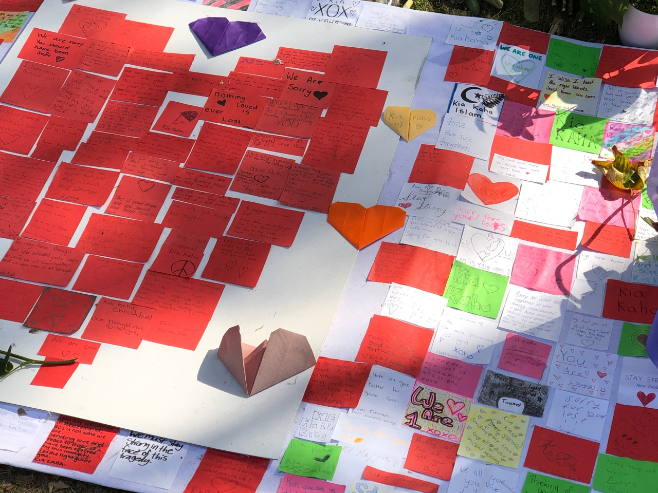 One board with red Post-It notes arranged in a heart shape with messages on it next to another board with other Post-It notes with more messages on it for the victims of the Christchurch terrorist attacks