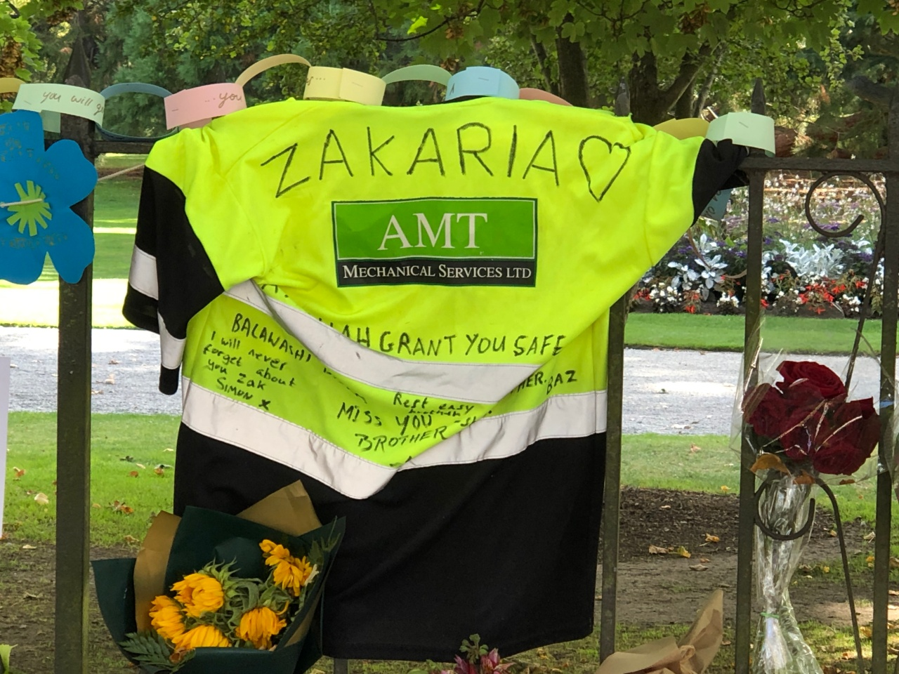 """A fluorescent vest for AMT Mechanical Services with the name """"Zakaria"""" and a heart drawn next to it on the back. Messages from his co-workers are written on the back. The vest hangs on a fence at the Christchurch Botanical Gardens. Zakaria was one of the 51 victims of the Christchurch terrorist attacks on mosques on 15 March 2019"""