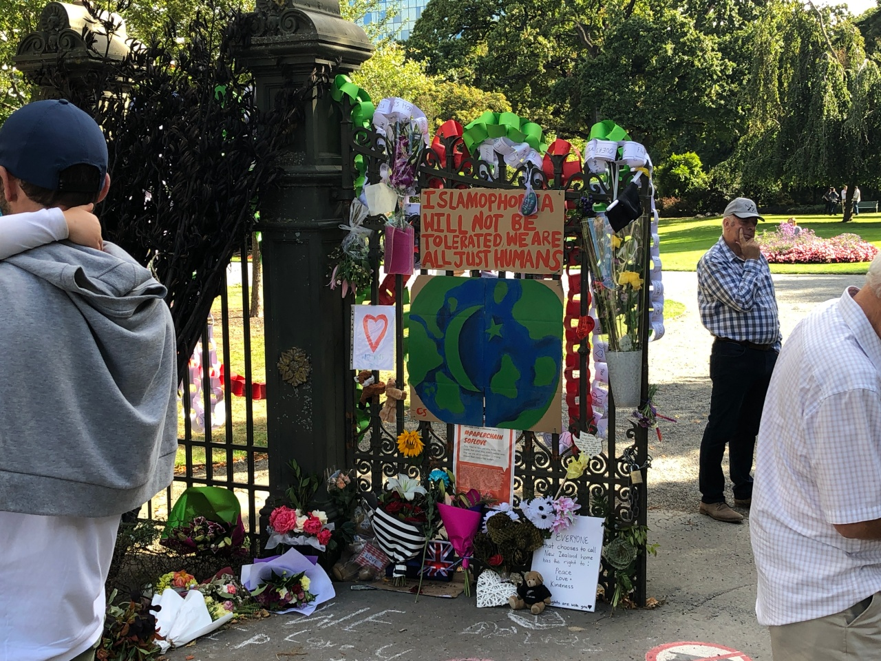 """Signs and decorations adorn the gates to the Christchurch Botanical Gardens. One reads, """"Islamophobia will not be tolerated. We are all just humans."""" These are signs and tributes to the victims of the Christchurch terrorists attacks."""