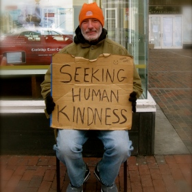 "Homeless man in warm clothing holding a sign saying, ""Seeking Human Kindness"""