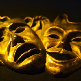 Gold tragedy and comedy masks intertwined laid down
