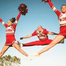 Cheerleaders Wearing Red and White Uniforms, Jumping in the Air
