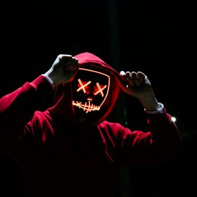 Man in red hoodie sweatshirt with electronic face in the dark