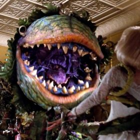 Audrey II Holds on Tight to Audrey While It Sings - Little Shop of Horrors