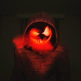 Evil face steaming in a red hoodie in a dark room