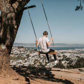 Photo of Man Wearing White Shirt While Sitting on Swing