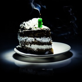 Sad lonely slice of birthday cake with a half-burnt candle on it