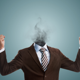 Man whose head has become smoke, holding his fists up, in a suit - burnout at work