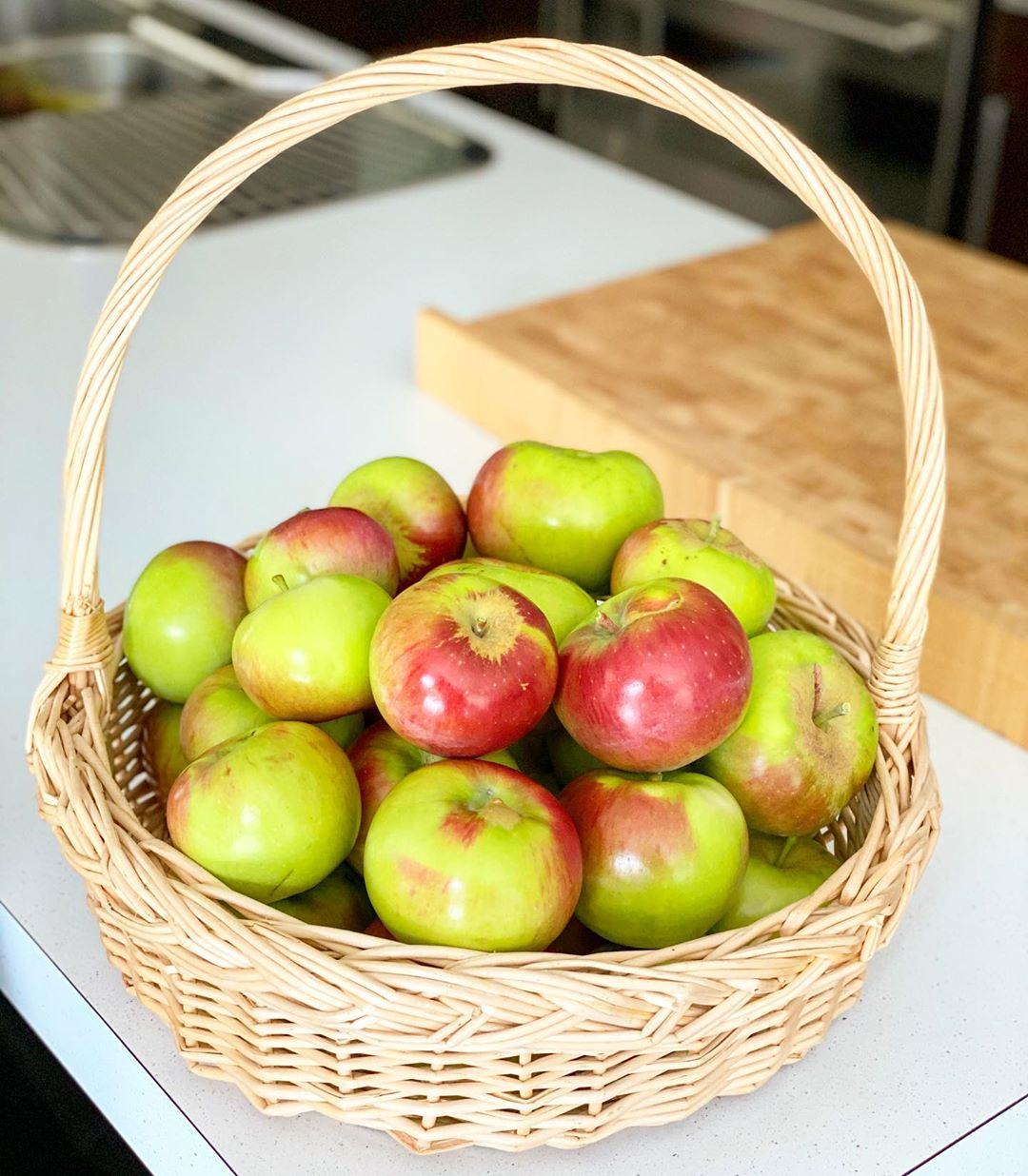 A wicker basket full of Peasgood's Nonsuch apples (a combination of green and red skinned apples)