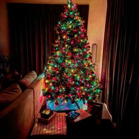 Traditional Christmas tree illuminated with red, yellow, green, and blue lights with crimson and gold ornaments on the tree. There are presents underneath the tree, some wrapped in reflective blue paper and some wrapped in red and gold striped paper