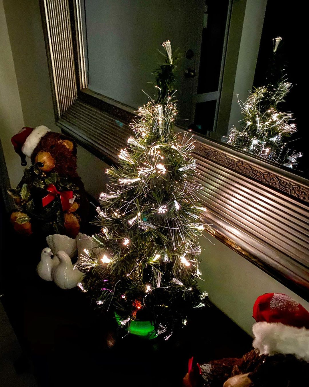 Small Christmas tree illuminated by fibre optic strands with two small teddy bears wearing Santa hats either side of it