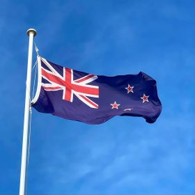 The New Zealand flag waves in the breeze with a blue sky behind it