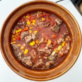Beef, onions, red peppers, yellow peppers, tomato pieces in a tomato sauce in a crockpot