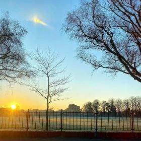 Sunrise over a boys' high school and its grounds with frost on it with a crisp blue sky and barren trees