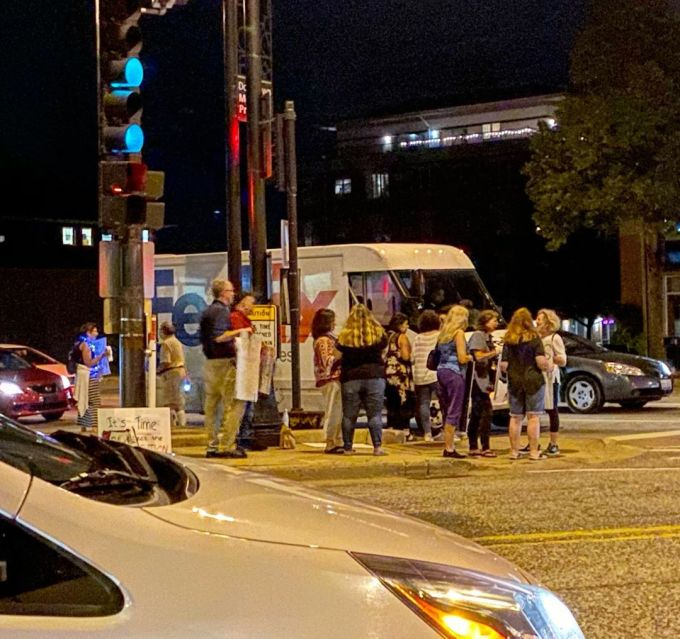 A group of people protesting the Presidency of Donald J Trump and demanding impeachment standing on a busy street corner in suburban Chicago