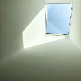 White skylight shaft somewhat in shadow leading to the skylight above with light blue sky beyond