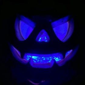 Blue glowing coming from the eyes, nose, and mouth in a fake carved Halloween pumpkin