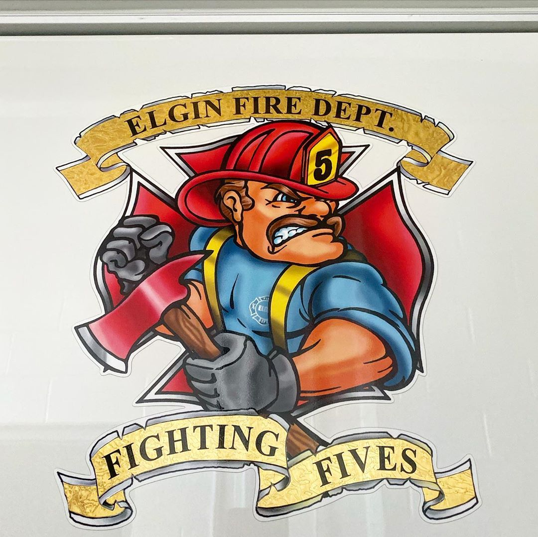 """Mascot of the Elgin Fire Department Number 5 station: Firefighter with a helmet on and axe in hand with """"Fighting Fives"""" below it"""