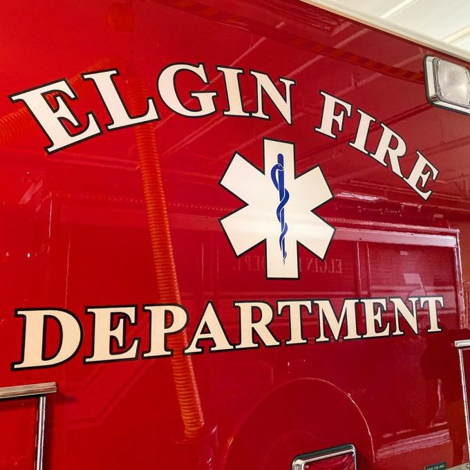 """Paramedic emblem and the words """"Elgin Fire Department"""" on a red ambulance"""