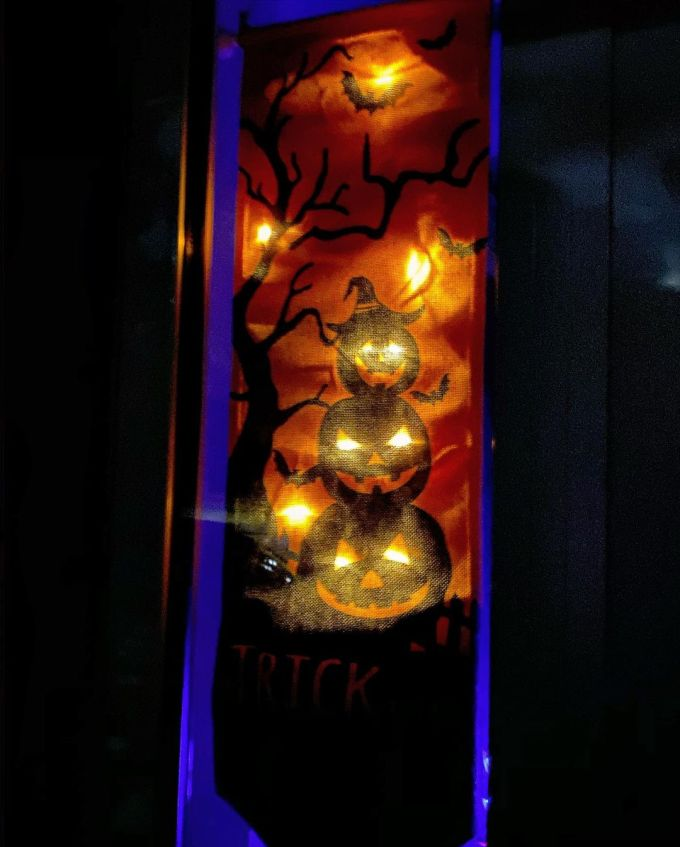 Halloween banner lit up with orange LED lights so Jack-O'-Lantern eyes glow and orange stars are in the sky with bats flying around