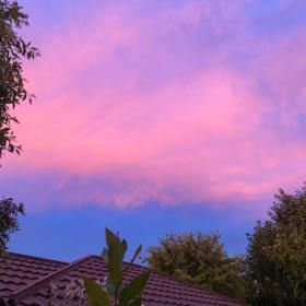 Dramatic blue, purple, salmon, coral, and pink clouds as the sunsets