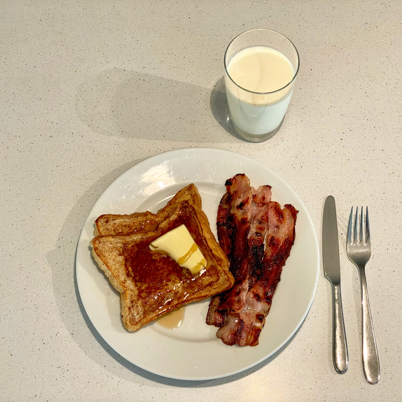 French toast with butter and syrup, and bacon, on a plate, with a knife and fork to the right and glass of milk above it