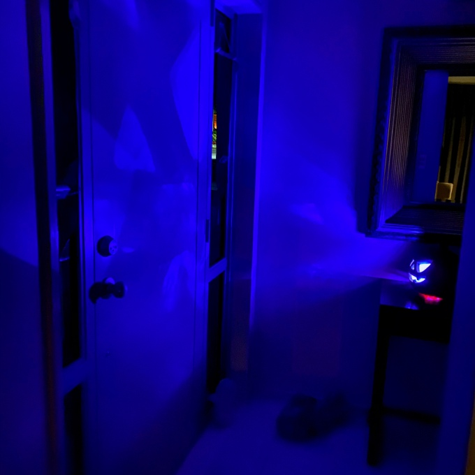 Jack-o'-Lantern glows with a blue light, casting shadows on the door and walls around it