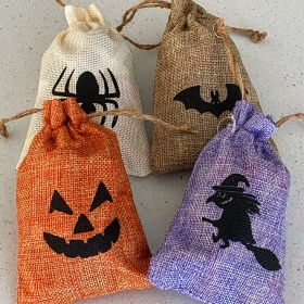 Four linen bags full of Halloween candy: Cream bag with a spider on it; Orange bag with a jack-o-lantern face on it; Brown bag with a bat on it; Purple bag with a witch on a broomstick on it