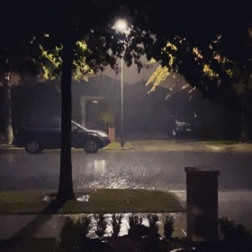 Heavy rain falling in the street outside the house